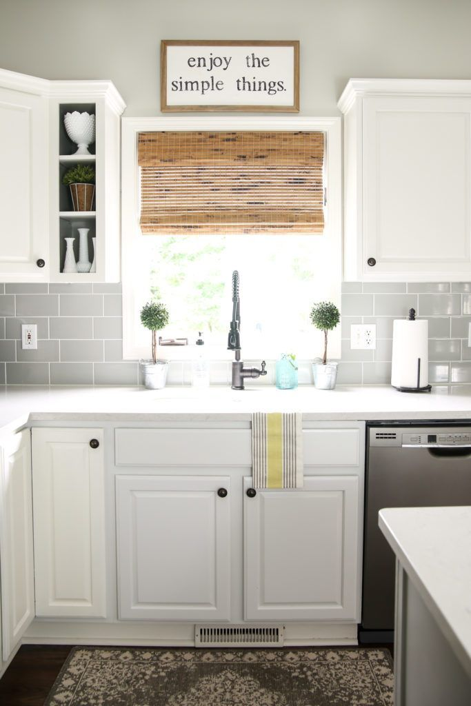 Modern Farmhouse Kitchen With Grey Subway Tile Backsplash White Cabinets And Bamboo Shade On Window Over Sink