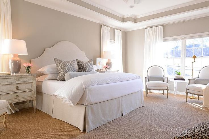 Beautiful cream and gray bedroom is clad in sisal carpeting and gray wall paint framing a white tray ceiling and features a cream arch headboard accenting a bed dressed in a cream pleated bedskirt and white hotel bedding topped with silver and gray trellis pillows paired with a dove gray bolster pillow.