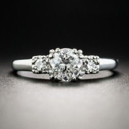 Traditional and timeless, this straight ahead three-stone diamond engagement ring, dating from the mid-20th-century, features an icy white and sparkling round brilliant-cut diamond, weighing .71 carat, accompanied by a GIA Diamond Grading Report stating: E color - VS2 clarity. The scintillating stone beams between a pair of small single-cut diamonds, all presented in a sleek hand-fabricated platinum mounting. Classic. Currently ring size 5 1/4.