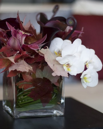 Modern Centerpiece  Sleek arrangements of burgundy blooms like cymbidium orchids combine with sugar-maple leaves for a rustic element.