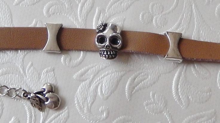 Een  L.Bruine  Armband  van imitatie leer  met mooie metalen schuifkralen Doodshooft/Schedel .Lengte  /- 19 cm te verlengen tot  /- 25 cm.