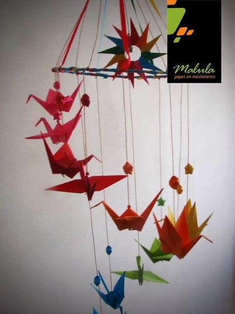 Arco Iris:  La línea Arco Iris de Malula, se caracteriza por los colores decrecientes, semejantes a un Arco Iris, Tirabuzones y Moviles con figuras con origami son protegonistas.    Moviles con figuras  Descripción: Líneas de 12 figuras en origami + 12 estrellas en origami + mándala estrellada,  realizados con papeles de colores de 15 x15 cm. Línea de 1,20 metros de largo.