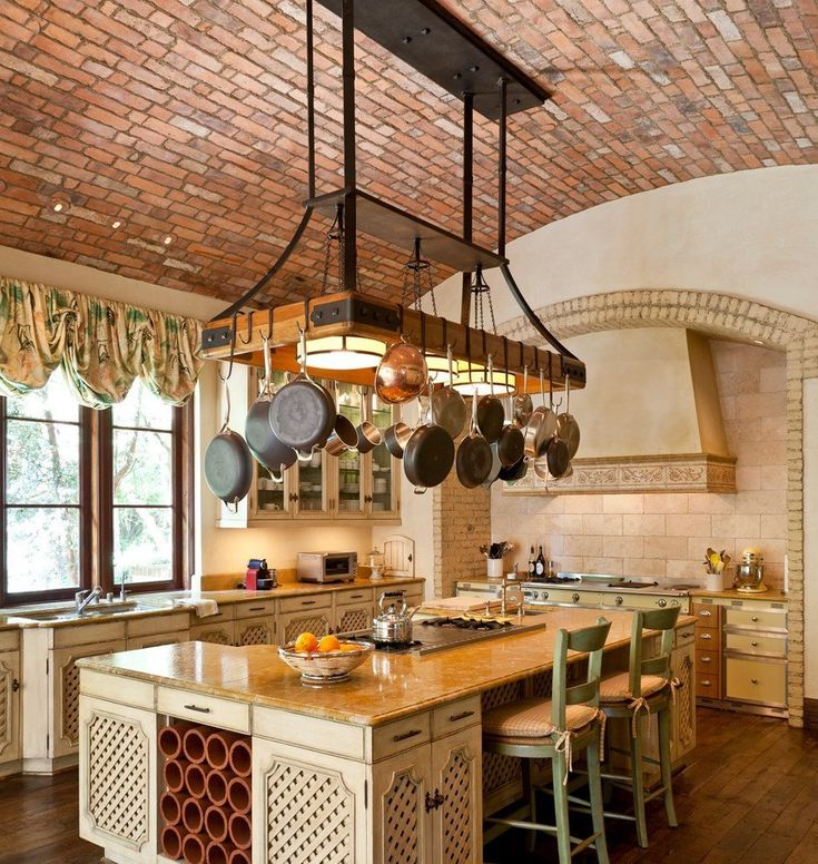 Pots and pans hanging over kitchen island. Love brick ceiling.