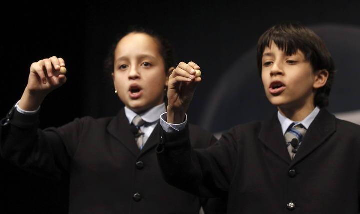 Los niños de San Ildefonso, Ismael Rastrelli y Sherley Fonseca, muestran el número 76.058 que ha sido agraciado con el premio Gordo, de 4 millones cada serie, en el Sorteo Extraordinario de Navidad que este año se celebra en el Teatro Real de Madrid. #LoteriaRTVE