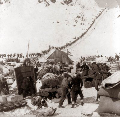 This photograph was taken in 1898, and shows miners who were part of the Klondike Gold Rush. Notice in the background the long ribbon of miners making their way up the snowy mountain.