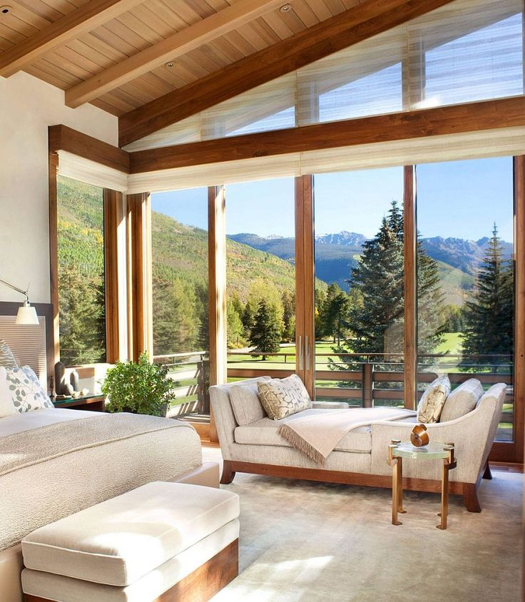 Corner windows of the bedroom with walnut trims open it up towards the mountain view outside