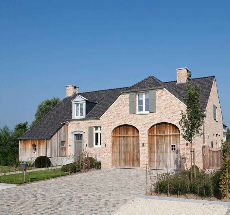 Deze landelijke villa geniet van zijn karakter dankzij het gebruik van gerecupereerde gevelmaterialen, het rieten dak, het gebruik van blauwe hardsteenn en het vergrijsde padoekhout.