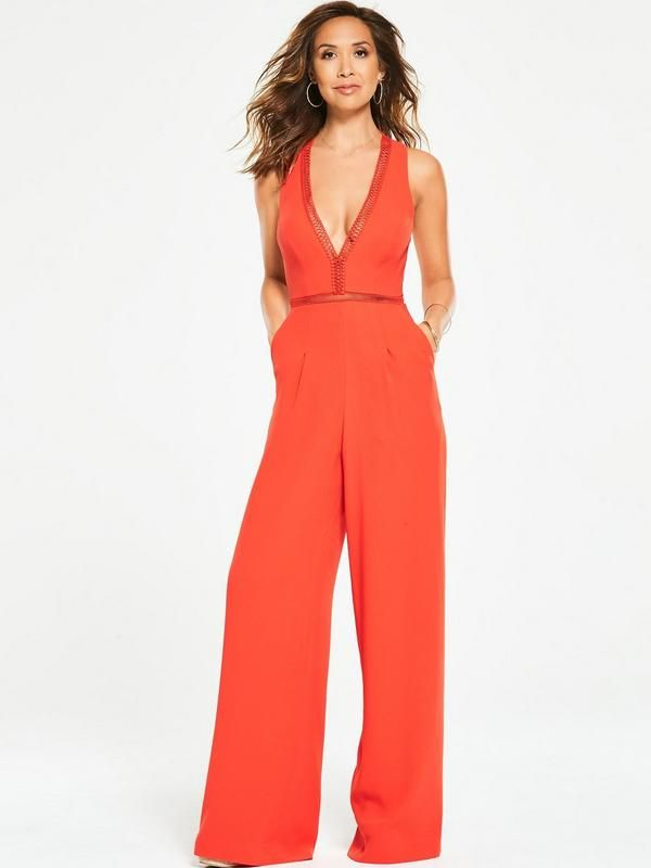 Myleene Klass Wide Leg Jumpsuit Showing how less is more, this classic jumpsuit by Myleene Klass is perfect for special occasions. The wide leg is a key trend for the season, while the plunging V-neckline is a sexy style touch that's a typical Myleene touch. Finished with sheer ladder trims to the waist and neckline and a zesty orange hue, this all-in-one is a sexy pick that's perfect for summer occasions!Add a pair of heels and gold metallic accessories to compliment the colour of th...