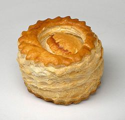"A vol-au-vent (pronounced [vɔlovɑ̃], French for ""windblown"" to describe its lightness) is a small hollow case of puff pastry. Vols-au-vent are typically made by cutting two circles in rolled out puff pastry, cutting a hole in one of them, then stacking the ring-shaped piece on top of the disc-shaped piece.[1] This pastry is usually found filled with savory ingredients, but can also have a sweet filling.  The first recipe was documented in 1739."