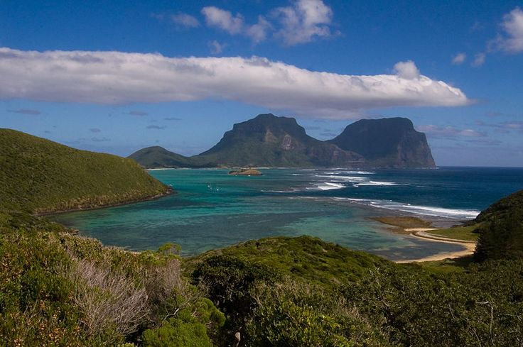 """Lord Howe Island is an irregularly crescent-shaped volcanic remnant in the Tasman Sea between Australia & New Zealand, 370 mi) east of mainland Port Macquarie. The island is about 10 km long & between 2.0 km & 3.0 km wide with an area of 14.55 km², """"of which only 398 hectares is in the lowland settled area"""". Along the west coast there is a sandy semi-enclosed sheltered coral reef lagoon. Most of the population lives in the north, while the south is dominated by forested hills"""