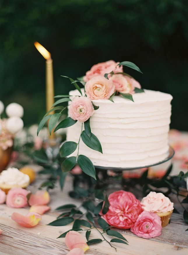 Simple cake with fresh flowers and cascading leaves.