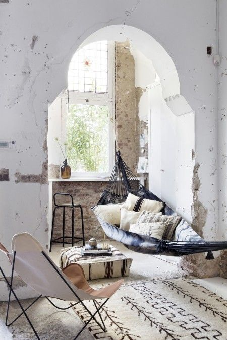 ethnic vibes living room hammock bat chair pouf floor pillow beni ourain rug industrial feel moroccan arch covered white old bottle as vase