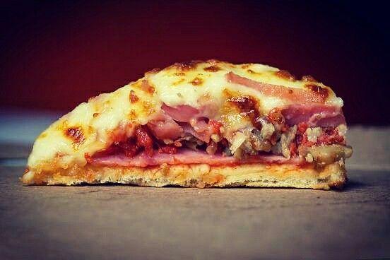 Rebanada de pizza cubierta de queso