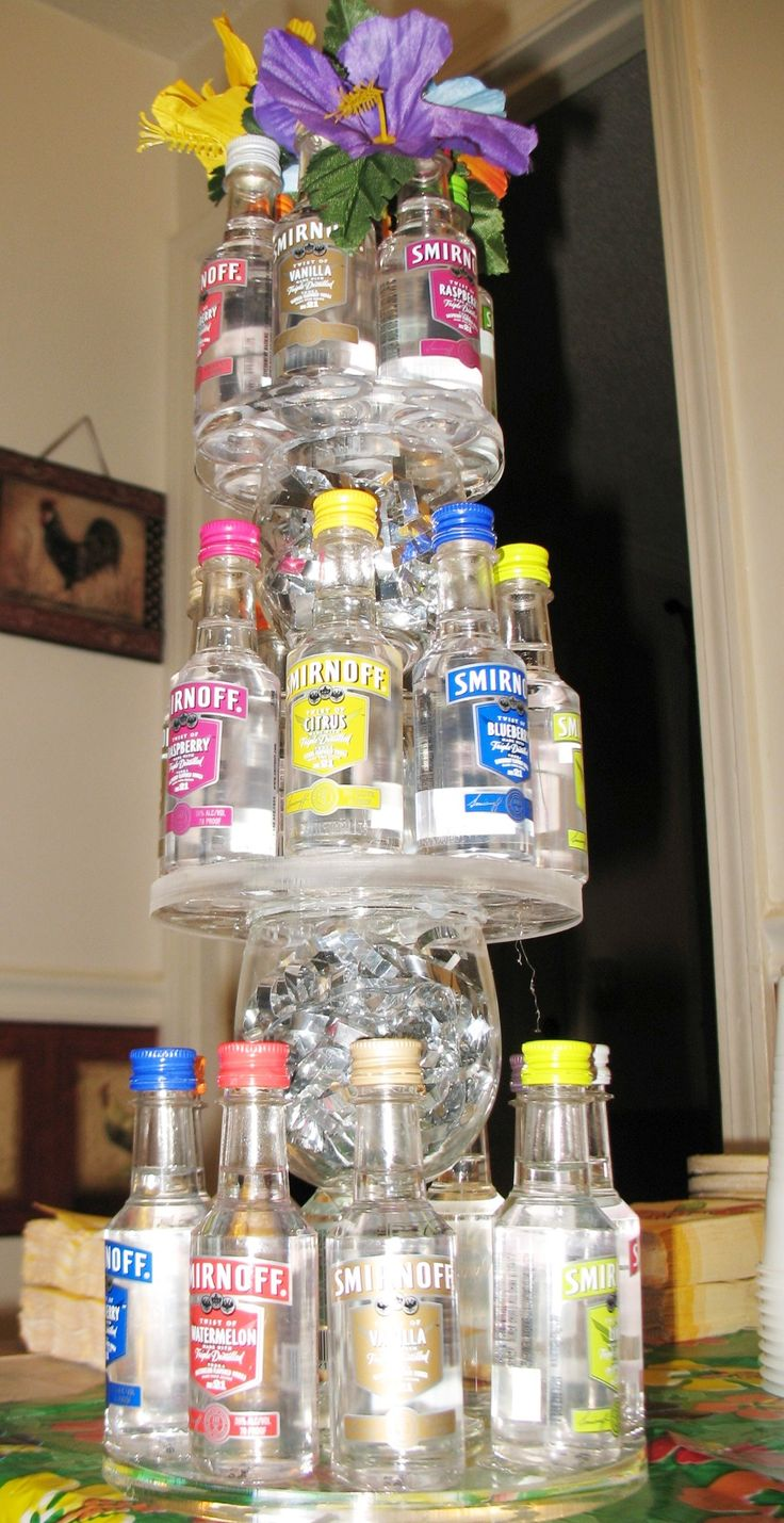 Vodka mini bottle tower centerpiece for a Luau themed stock-the-bar engagement party. This is all just mini bottles hot glued to acrylic circles with wine glasses used for risers.  Nothin' to it :-)  If you don't have acrylic to use as a base, I imagine foam board covered in paper or fabric would work just as well.