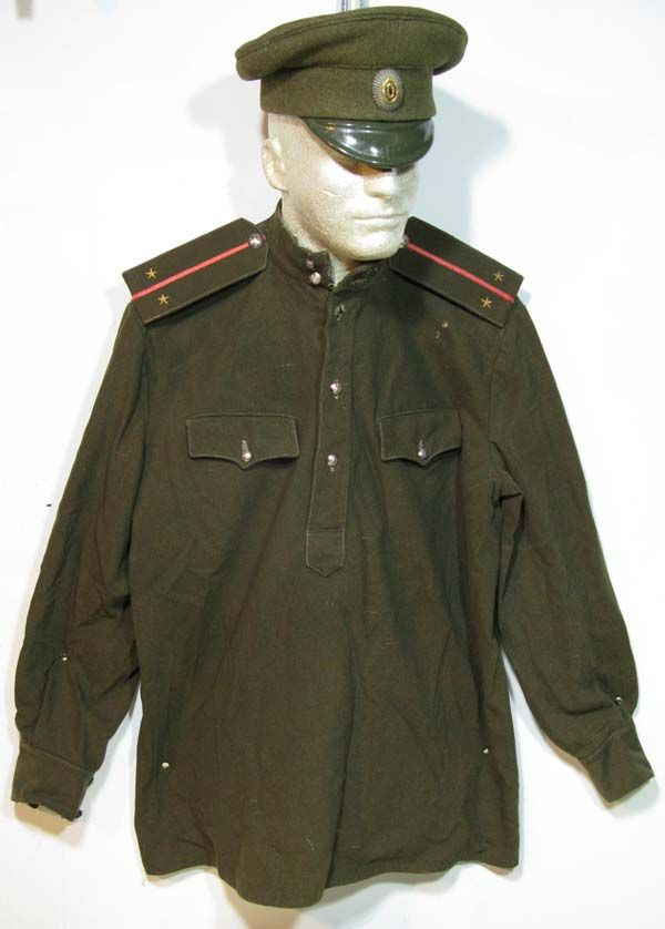 Imperial Russian Army - Sub-Lieutenant's field uniform/shirt. Buttoned pocket flaps with single, shallow scallop. Shoulder boards with two gold stars and center line piping are a Sub-Lieutenant's  rank insignia. Note oval cap badge. WWI.