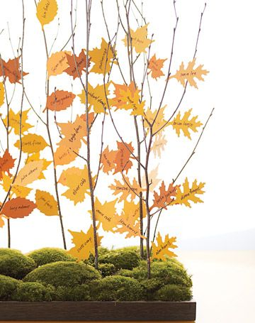 For a rustic autumn wedding, craft-punched bright paper leaves bearing guests' names transform bare branches into majestic trees; we cut slits into the branches with a craft knife and then slid in the leaves.