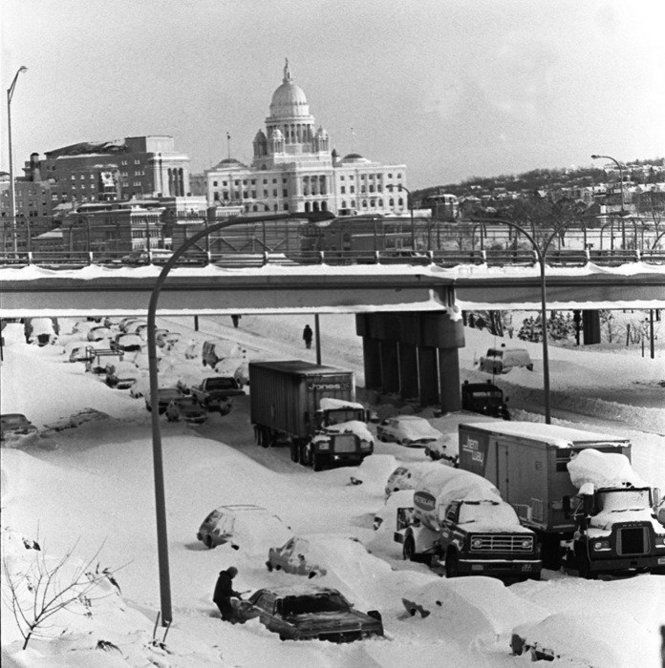 A motorist clears snow from his stuck car in the southbound lane of Interstate 95 outside of Providence, R.I., on Feb. 7, 1978, the day after the 1978 blizzard began. The 24-hour storm that pounded the Northeast, crippled Rhode Island for more than a week, cutting off power, closing the airport and straining state resources