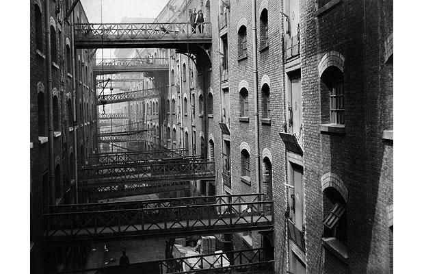 Shad Thames, c1910. Much of the river Thames was lined by vertiginous warehouses creating dark canyons separated by slit-like alleys leading to ancient stairs, jetties and wharves. At Shad Thames a myriad of iron bridges spanned the street to allow goods to be moved across the walkways to warehouses inland.