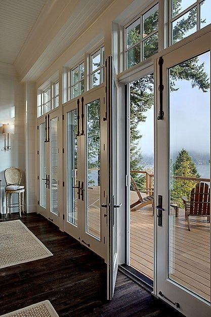 Gorgeous rustic chic white glass paned doors leading to the back deck.  From a 4-story Craftsman style home construction by Lavallee Construction, discovered on Porch.com
