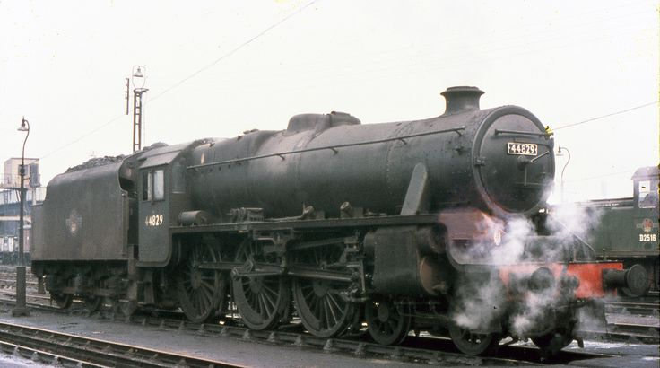 April 10th 1968 9K Bolton mpd Looking very respectable considering the date, Stanier Black 5 4-6-0 44829 stands outside the depot at Bolton. This engine, built in 1944, served at many depots including Bristol Barrrow Road, Toton, Monument Lane, Bushbury, Holyhead, Saltley, Crewe South and Workington before arriving at Bolton during January 1968. Behind is Hudswell Clarke shunter D2516, formerly of Workington, awaiting removal to C.F. Booths Ref B1-19