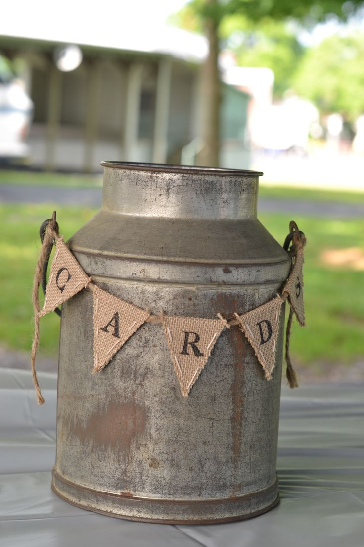 An old galvanized milk can as a card holder. Hand made, stamped burlap bunting.