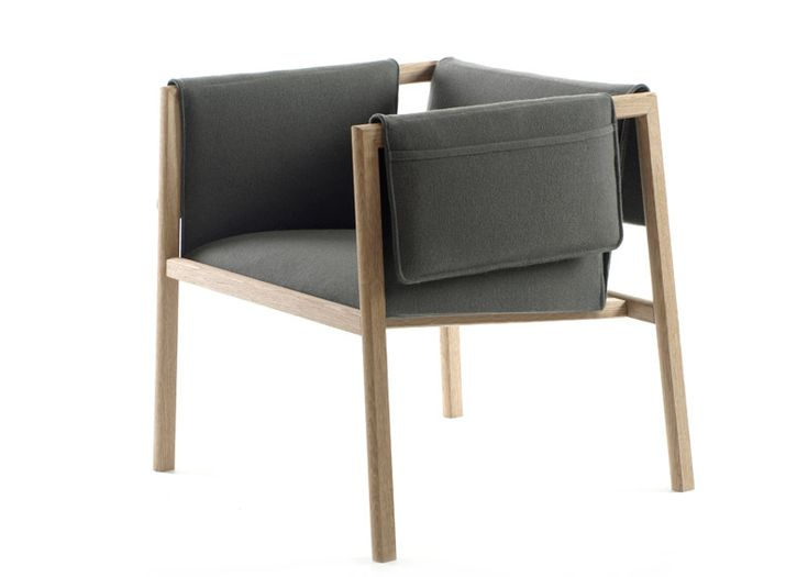 Pockets for TV remotes, newspapers and tablets hang over the arms of this wooden-framed chair by Norwegian design collective Angell, Wyller & Aarseth.
