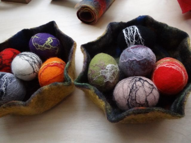 Felt eggs with silk fibres in felted basket.