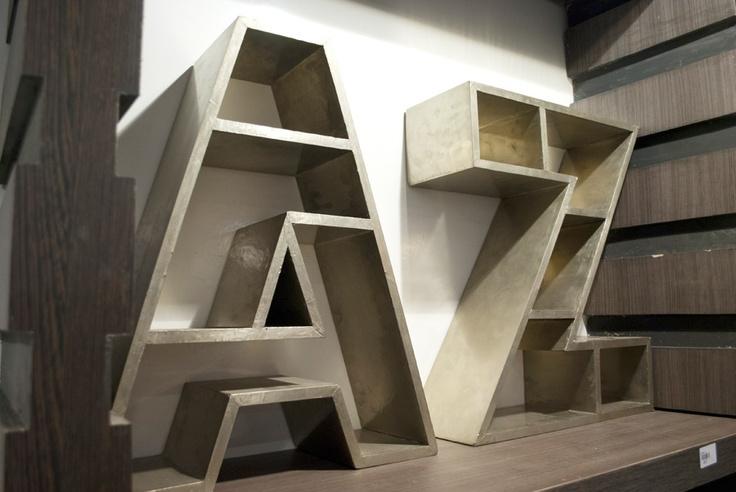 As estantes de letras, da Formas Coloridas, são de madeira e folha de alumínio envelhecido. Tem 48 x 18 x 60 cm* de tamanho e divisórias para acomodar objetos maiores e os menorzinhos também.