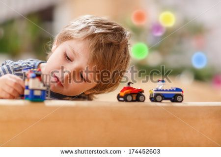 Little blond boy playing with cars and toys at home, indoor - stock photo