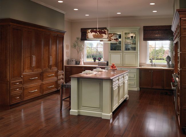 Cabinetry in two colors draws attention to the china cabinet and island with chairs - Kraftmaid bathroom cabinets catalog ...