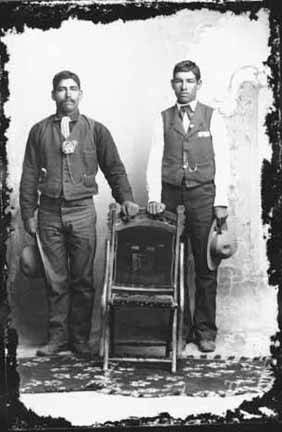 Father and son in studio, mining area of Hillsboro and Kingston, New Mexico, ca. 1885 - 1890, by J.C. Burge. Palace of the Governors Photo Archives 076219.