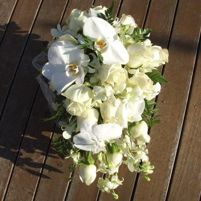 Phalaenopsis Orchids, white with yellow center mixed with Roses and Spiral Gum Leaves