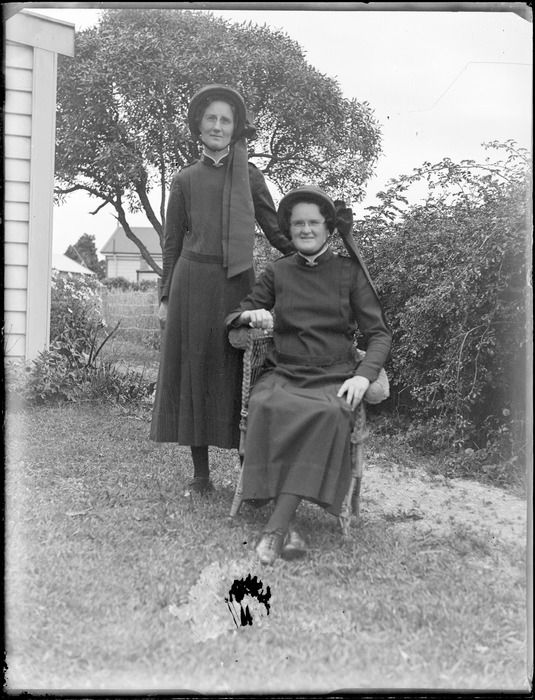Group of women, two [Salvation Army?] women in uniform, one standing and one seated in cane chair, garden lawn area, Hawke's Bay District c1930