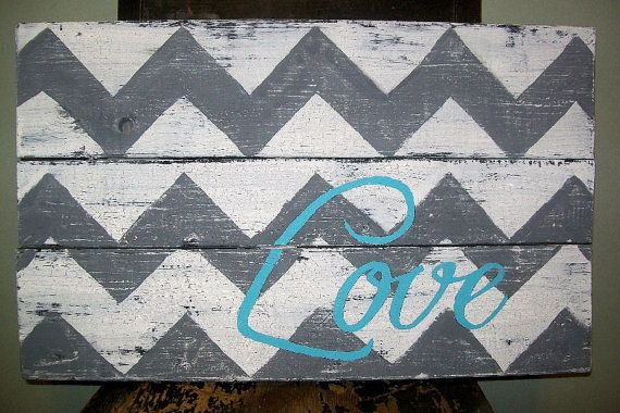 Wood sign that is approximately 23 inches wide and 16 inches tall, made from pallet wood, rustic, primitive, and distressed. Currently I am making these as the order comes in. There is an approximate wait time of 2 weeks before it would ship.  I painted it in white with medium gray chevron stripes. I hand painted the love on the sign in a turquoise blue.   It is unfinished on the back and has a wire hanger for putting the sign up on the wall. The sign would also be cute resting against the…