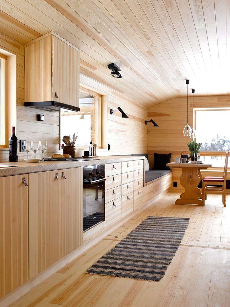SITTEBENK: Kjøkkenbenken trappes ned og blir til sittebenk ved spisebordet. Ensartet materialbruk på innredning, gulv, vegg og tak gir et rolig uttrykk.