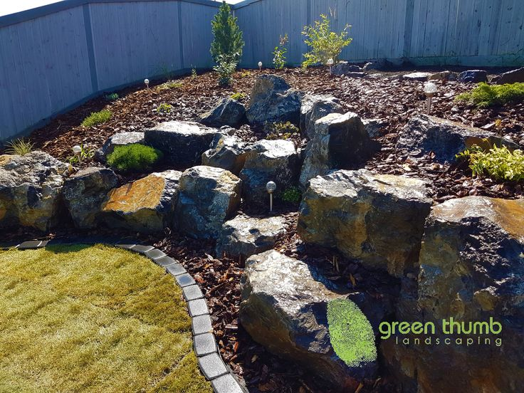 A boulder rock garden with medium bark mulch and cobblestone edging.  With an extreme elevation in your backyard, we can help you maximize your space with a nature-scaped boulder retaining wall. It's like coming home to the mountains in your backyard!
