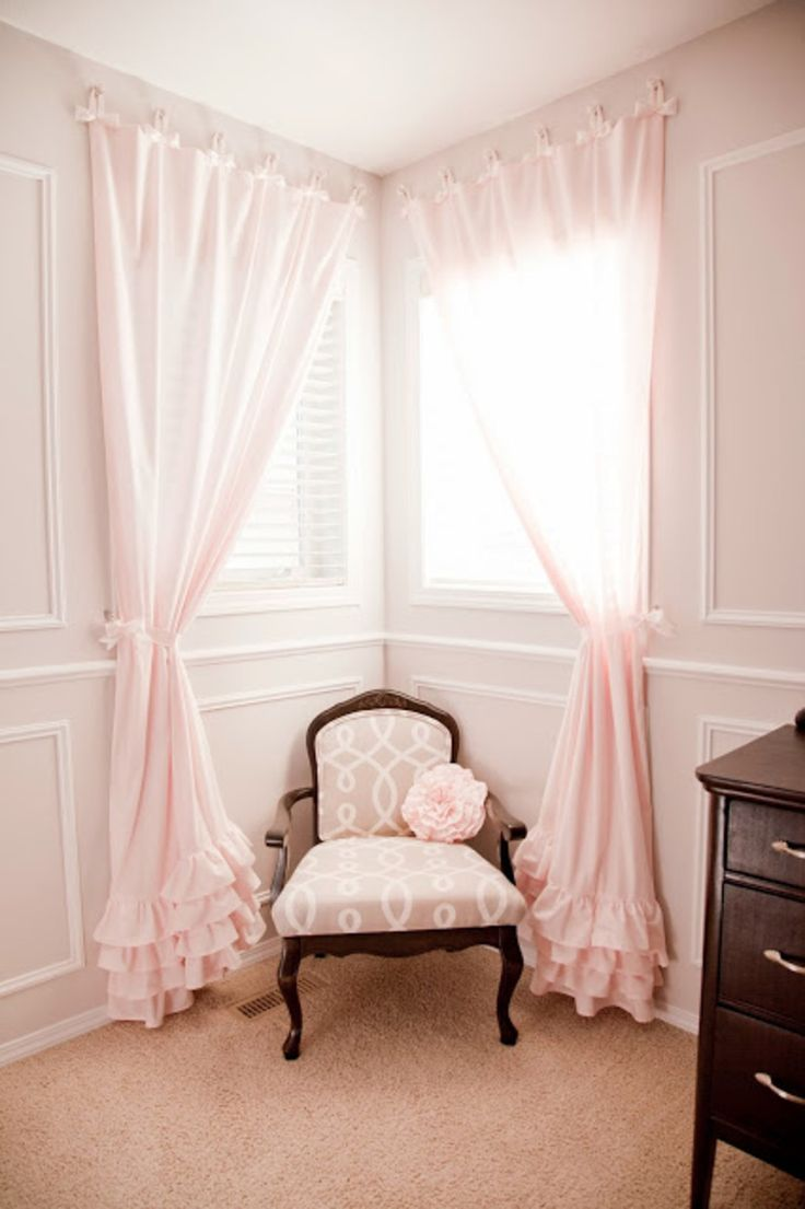 To open up your cornered windows, hang one curtain on the outside of the frame to make your windows look like one cohesive unit. A pair of ruffled curtains add an extra element of detail that make this little girl's room a perfect reading corner for bedtime stories.