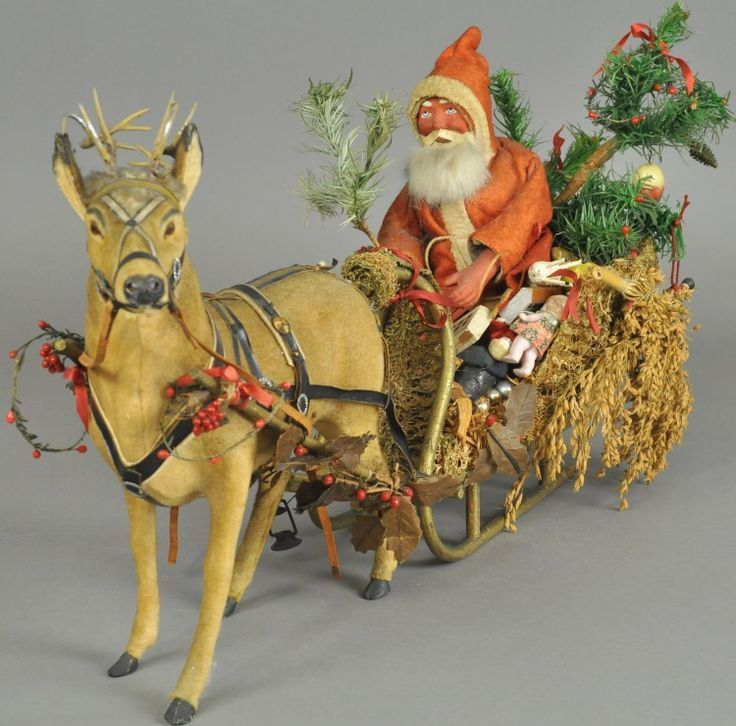 Germany, magnificent lichen moss sleigh, loaded with toys, many Erzgebirge pieces, tiny bisque dolls, children on sleighs, basket of wax fruit, and two tier feather tree rests behind an all original Santa, dressed in red coat, composition head with rabbit fur beard, holding feather tree. Brown glass eye reindeer is pulling the heavily laden sleigh, harness is leather trimmed with Dresden buckles, wood yoke trimmed with red holly berry, upright ears and lead antlers top off this noble…