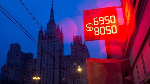 A U.S. dollar symbol sits on a neon sign displaying the latest Russian ruble euro dollar exchange rate outside a currency exchange bureau in Moscow, Russia, on Tuesday, Dec. 16, 2014. The ruble sank to a record, deepening Russia's currency crisis, as people scrambled to convert their money into dollars after a surprise interest-rate increase failed to shore up investor confidence. Photographer: Andrey Rudakov/Bloomberg.