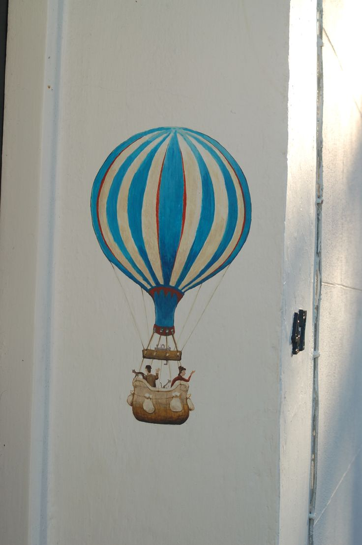 Sticker of a air balloon the outside of someone's door  show that the people who are in that are flying away somewhere and the colours used are bright and see able with blue and hints of red and yellow.