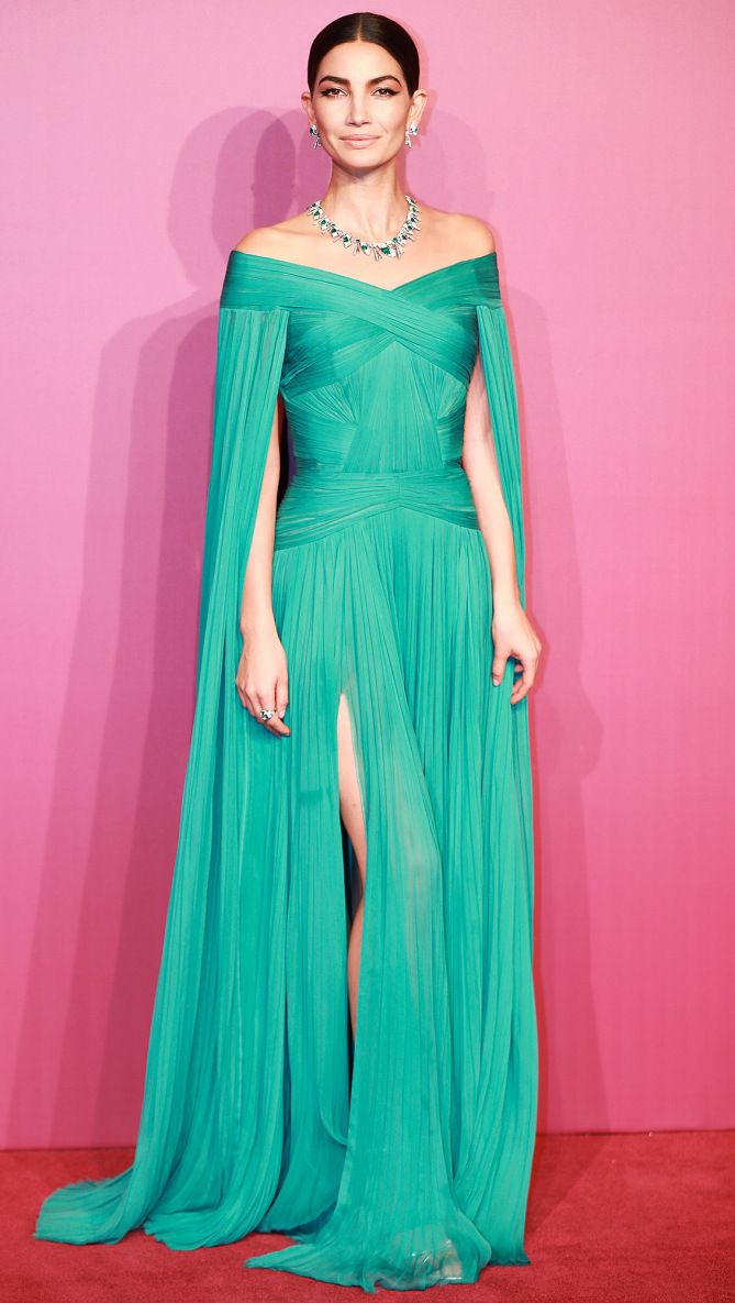 Lily Aldridge is wearing a turquoise off shoulder J. Mendel gown with a cape and slit. Classy and elegant! I like the matching jewelry!
