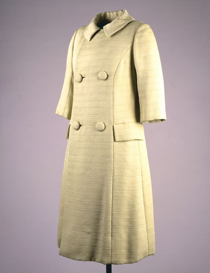 Oleg Cassini (American, b. France, 1913-2006) Medium: Silk, wool,  A three-piece dress and coat ensemble. The dress consists of a two-piece ensemble in beige silk and wool with a shell top and a pleated A-line skirt. The coat is beige silk and wool ribbed ottoman, with four cloth-covered buttons. Historical Note: This outfit was worn by First Lady Jacqueline Kennedy during her State visit to Canada at a lunch with Prime Minister John Diefenbaker on May 17, 1961.
