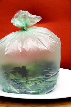 Divide your big container of greens into two to four smaller plastic bags. Close the top of each bag lightly with your fist, blow into the bag, and fill it with air (carbon dioxide). Then seal the bag by twisting the top a few times before closing it firmly with a twist tie. Place it in the fridge, and your greens are good to go.