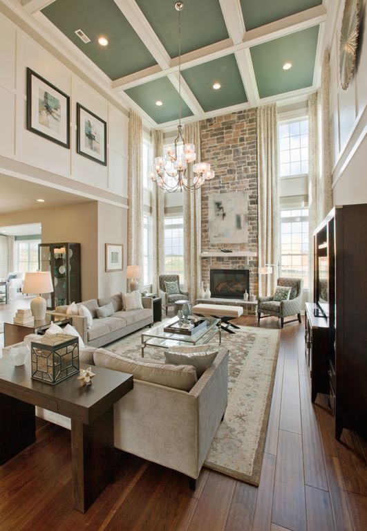 Living Room With High Ceilings And Fireplace With Windows