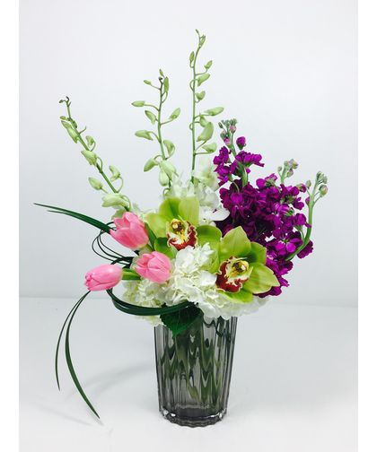 Dancing Elegance-White Hydrangea, pink tulips, fushia stock, dendrobium and cymbidium orchids in a clear vase.  #SpringFlowers #KansasCityFlowers #ToblersFlowers