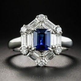 Classic geometric Art Deco design influences shine through in this chic and sophisticated estate jewel, highlighting a majestic royal blue Ceylon sapphire weighing 1.30 carats. The emerald-cut gemstone is strikingly presented in a lozenge- shaped frame composed of gleaming baguette diamonds and small round brilliant-cut diamonds, totaling one carat (.99 ct), artfully arrayed in a two-tiered border. 5/8 by 1/2 inch, currently ring size 6 1/4 +.