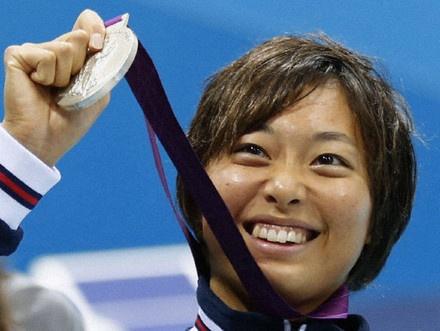 女子200メートル平泳ぎで獲得した銀メダルを、笑顔で掲げる鈴木聡美=水泳センター