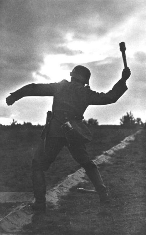 German soldier throwing an M24 hand grenade in WWII