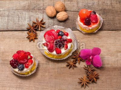 delicious cupcakes with berries over wood