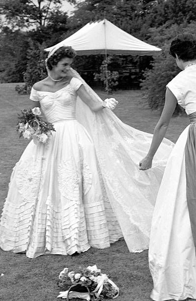 Socialite Jacqueline Bouvier fixing veil of wedding dress outdoors at Hammersmith Farm on day of her marriage to Sen. John Kennedy.